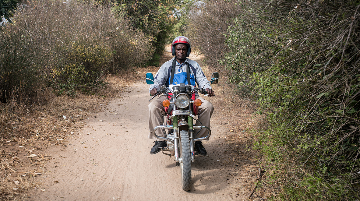 He rides his family's bike to a remote village 26 kilometers away, where he will screen people for TB and check on those on treatment.<br /><i>The Global Fund / Nichole Sobecki</i>