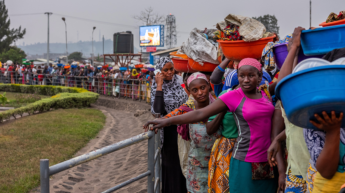 A line of people wait to cross the border from Goma, DRC, to Gisenyi, Rwanda, as a screen showing Ebola awareness messages plays behind them. Rwanda has a detailed national preparedness plan in place to fight Ebola. (Nichole Sobecki / VII for the Global Fund)