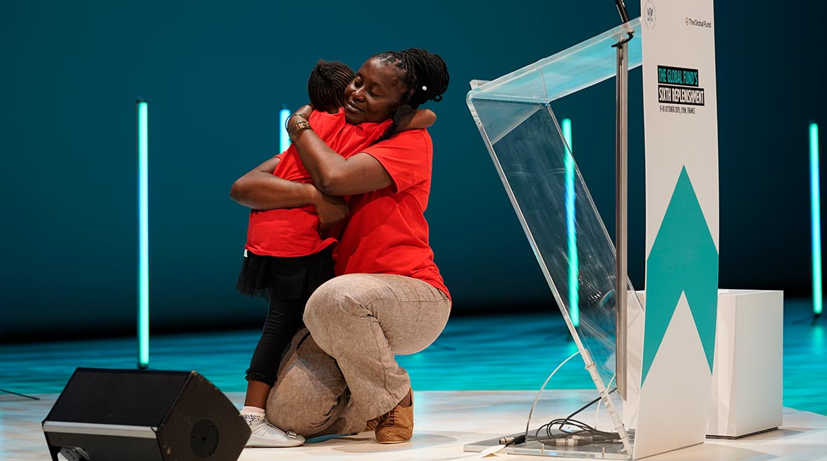 (RED) Ambassador Connie Mudenda embraces her daughter on stage at the Global Fund's Sixth Replenishment Conference in Lyon, France 9 October 2019.