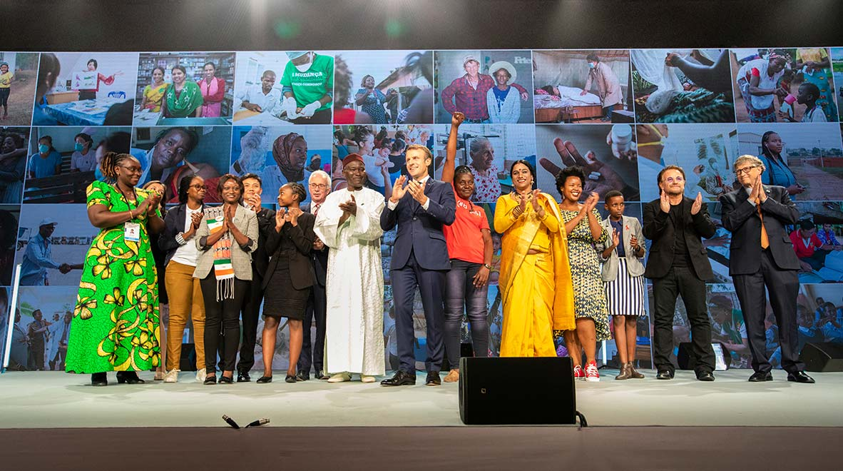 Supporters of the Global Fund celebrate at the successful conclusion of the Global Fund's Sixth Replenishment Conference 10 October 2019. From left to right: Maurine Murenga, Olya Klymenko, Phumeza Tisile, Zeinabou Idé, Saw Winn Tun, Joyce Amondi Ouma, Peter Sands, Elhadj Diop, President Macron of France, Connie Mudenda, Abhina Aher, Dr. Zolelwa Sifumba, Amanda Dushime, Bono, Bill Gates.